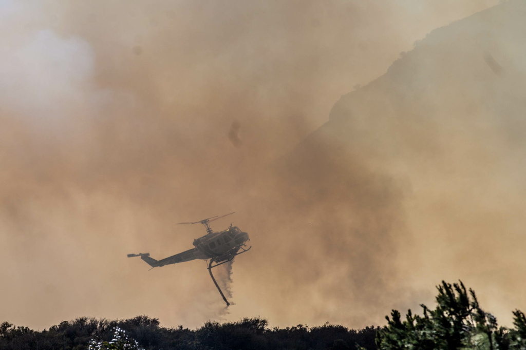 A helicopter from Kern County drops water on a brushfire in the unincorporated Newbury Park neighborhood west of Thousand Oaks in Ventura County.