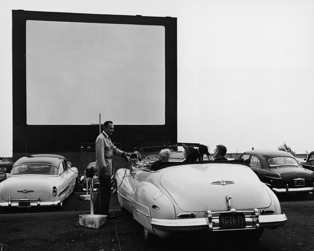 A uniformed drive-in theater attendant hands a clip-on speaker to the driver of convertible while the car's other passengers watch, New York, early 1950s.