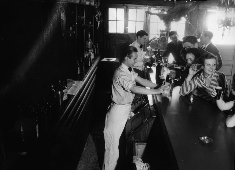 Two bartenders serve patrons at the Malamute Saloon, which was reportedly the first bar to open in Los Angeles after the 1933 repeal of Prohibition.