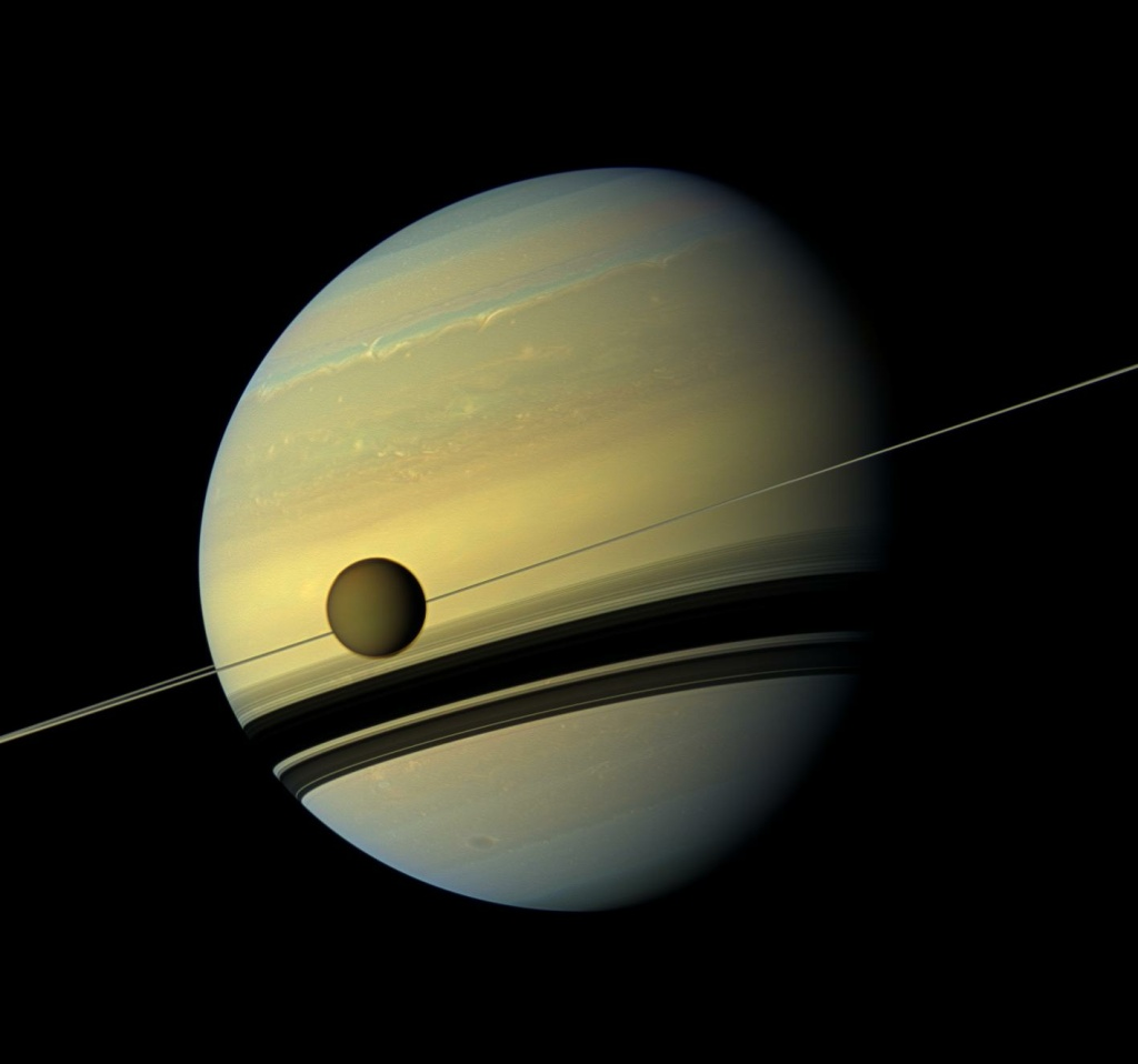 A giant of a moon appears before a giant of a planet undergoing seasonal changes in this natural color view of Titan and Saturn from NASA's Cassini spacecraft. Titan, Saturn's largest moon, measures 3,200 miles across and is larger than the planet Mercury. As the seasons have changed in the Saturnian system, and spring has come to the north and autumn to the south, the azure blue in the northern Saturnian hemisphere that greeted Cassini upon its arrival in 2004 is now fading. The southern hemisphere, in its approach to winter, is taking on a bluish hue. This mosaic combines six images — two each of red, green and blue spectral filters. The images were obtained by Cassini's wide-angle camera on May 6, 2012, at a distance of approximately 483,000 miles from Titan.