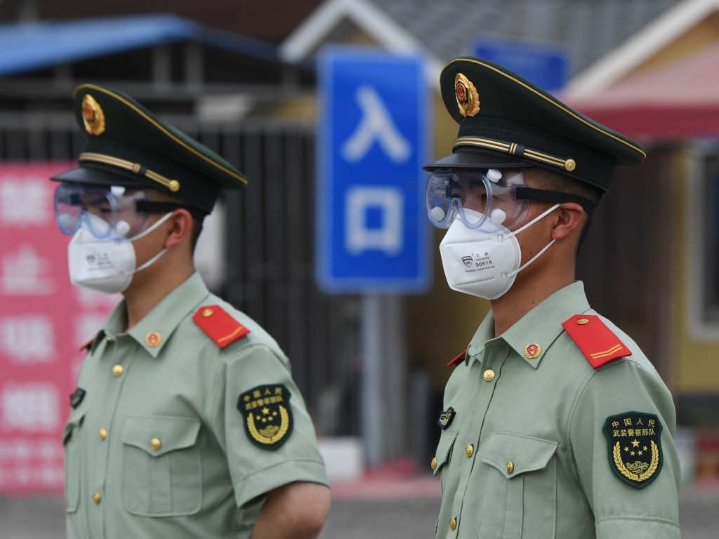 Paramilitary police officers wear face masks and goggles as they stand guard at an entrance to the closed Xinfadi market in Beijing on June 13, 2020.