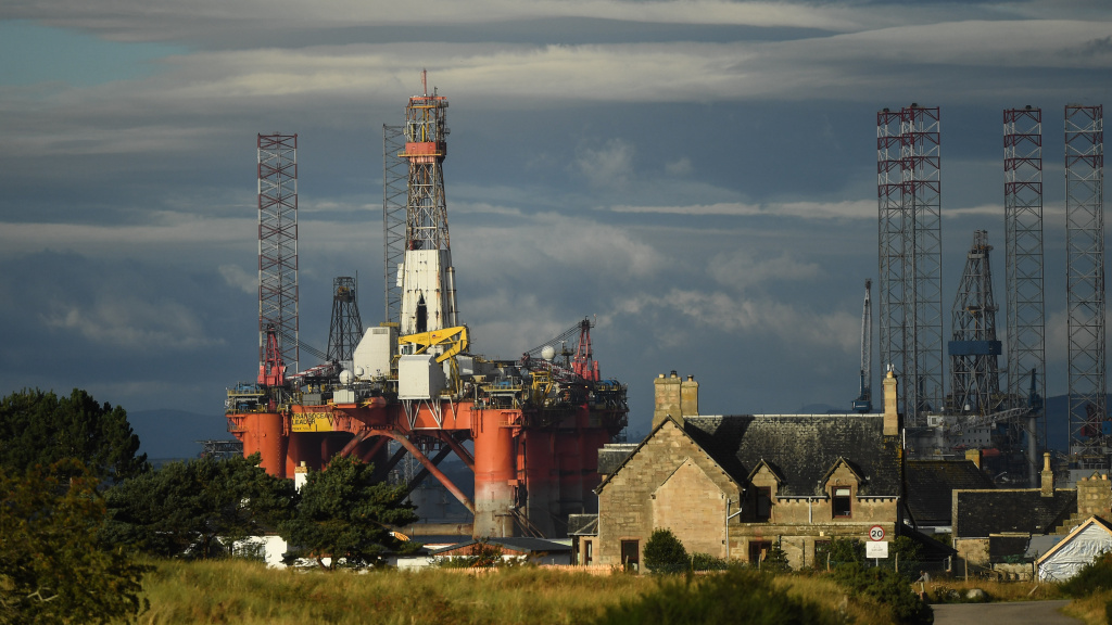 An oil rig towers over houses last week in Nigg, Scotland. Major players in the oil industry expect depressed oil demand and low prices to continue well into next year.