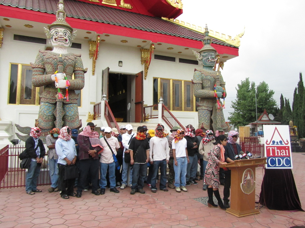 Two dozen Thai farm workers gather at the Wat Thai of Los Angeles.  Panida Rzonca with the Thai Community Development Center translates for a worker identified as