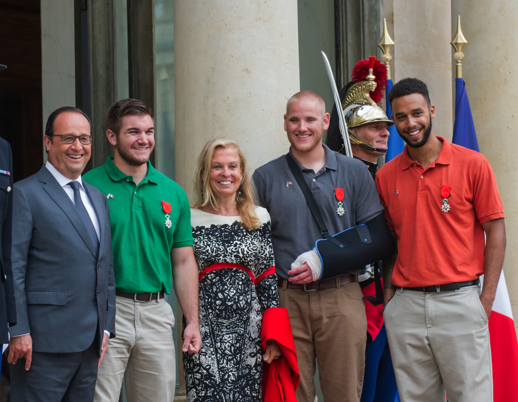 From left : French President, Francois Hollande, U.S. National Guardsman from Roseburg, Oregon, Alek Skarlatos, U.S. Ambassador to France Jane D. Hartley, U.S. Airman Spencer Stone and Anthony Sadler, a senior at Sacramento University in California, pose for photographers as they leave the Elysee Palace in Paris, France, after being awarded with the French Legion of Honor by French President, Francois Hollande, Monday, Aug. 24, 2015. French President Francois Hollande and a bevy of officials are presenting the Americans with the prestigious Legion of Honor on Monday. The three American travelers say they relied on gut instinct and a close bond forged over years of friendship as they took down a heavily armed man on a passenger train speeding through Belgium. (AP Photo/Kamil Zihnioglu)