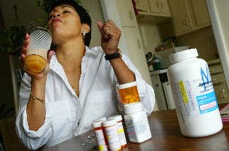 Alba Cerrato swallows some of her 14 different AIDS medications that she takes three times a day July 11, 2002 in Miami, Florida.