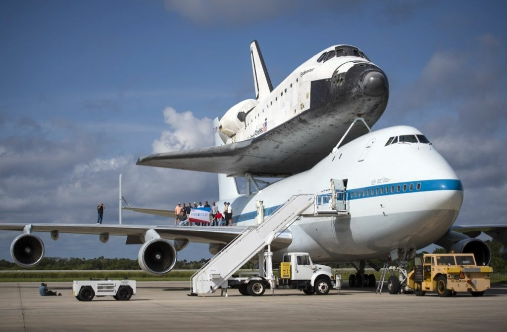 In this handout provided by NASA, Workers pose for a photograph on the wing of NASA's Shuttle Carrier Aircraft, or SCA, with the space shuttle Endeavour mated on top, at the NASA Kennedy Space Center, Shuttle Landing Facility on Sept. 18, 2012 in Cape Canaveral, Florida.