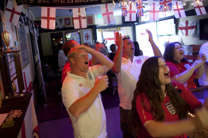 England fans Kevin Elson, left, Scott Kelly, center, and Jennifer Langford, bottom right, react while watching the last friendly game between England and Honduras ahead of the World Cup in early June. They watched the game at the The British & Dominion Social Club in Garden Grove.