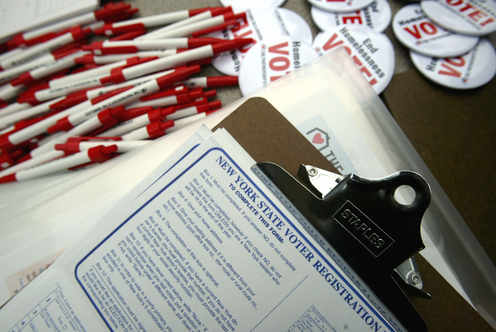 Pens, buttons and registration forms lie on a table during a voter registration drive sponsored by The Partnership for the Homeless in New York City.