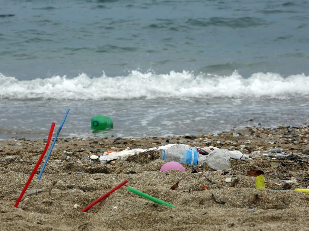 Plastic garbage lying on the Aegean sea beach in Greece.