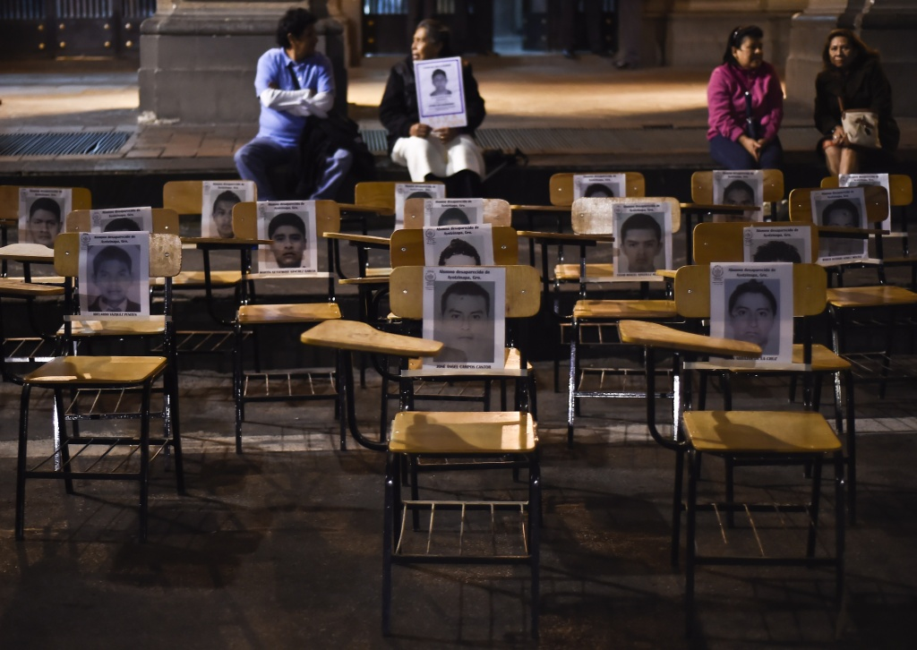 Chairs with portraits of missing students are seen during a march demanding justice for the 43 missing students along a street in Mexico City on October 22, 2014. Mexican authorities ordered the arrest of the mayor of the city of Iguala, Jose Luis Abarca, his wife and an aide, charging them with masterminding last month's attack that left six students dead and 43 missing.