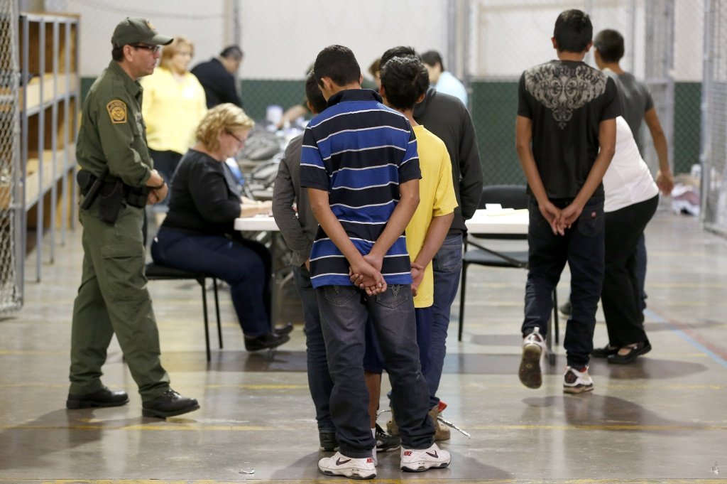 Boys wait in line to make a phone call as they are joined by hundreds of mostly Central American immigrant children that are being processed and held at the U.S. Customs and Border Protection Nogales Placement Center on June 18, 2014, in Nogales, Arizona.