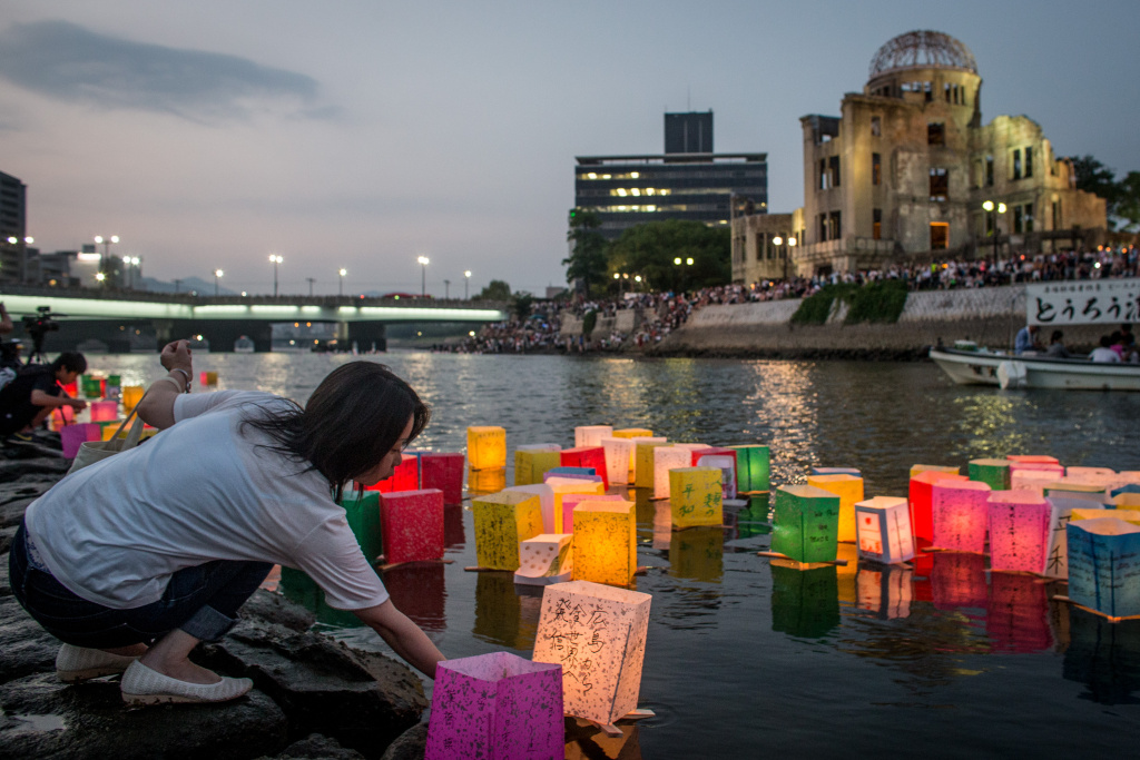 A woman places a candle lit paper lantern on the river during 70th anniversary activities, commemorating the atomic bombing of Hiroshima at the Hiroshima Peace Memorial Park.