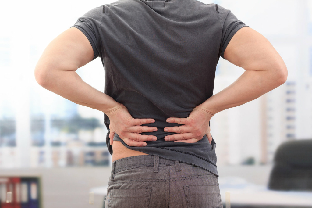 A man massaging his lower back pain.
