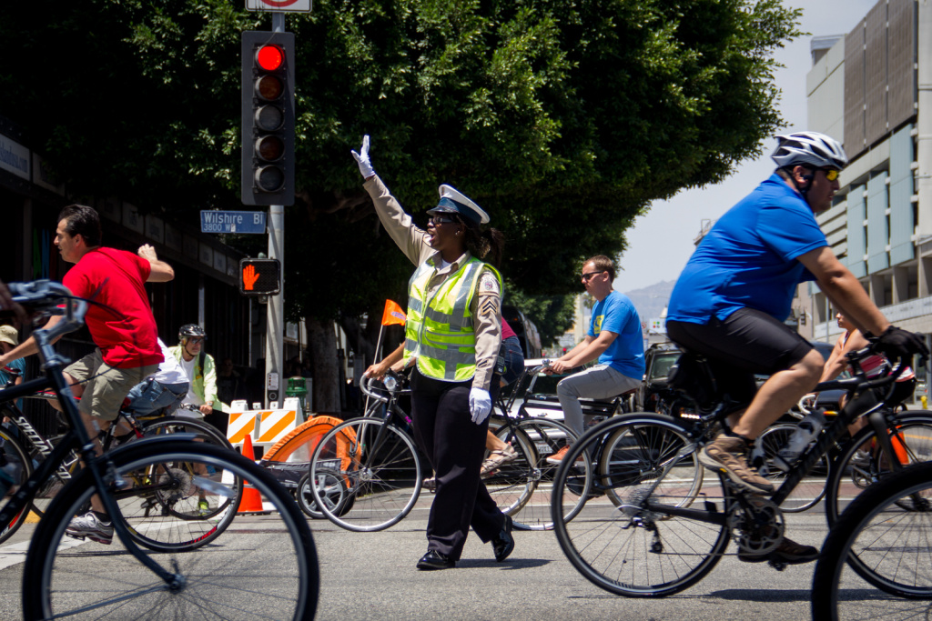 A safety officer directs traffic at a vehicle crossing point at Wilshire Boulevard and Western Avenue during CicLAvia on June 23, 2013.