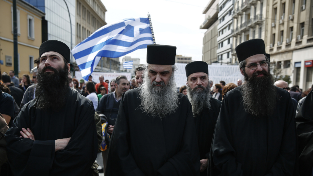 Greek Orthodox priests, seen during a rally in Athens earlier this year. On Tuesday Greek Orthodox Archbishop Ieronymos agreed with the prime minister to remove roughly 10,000 priests and staff from the state payroll.