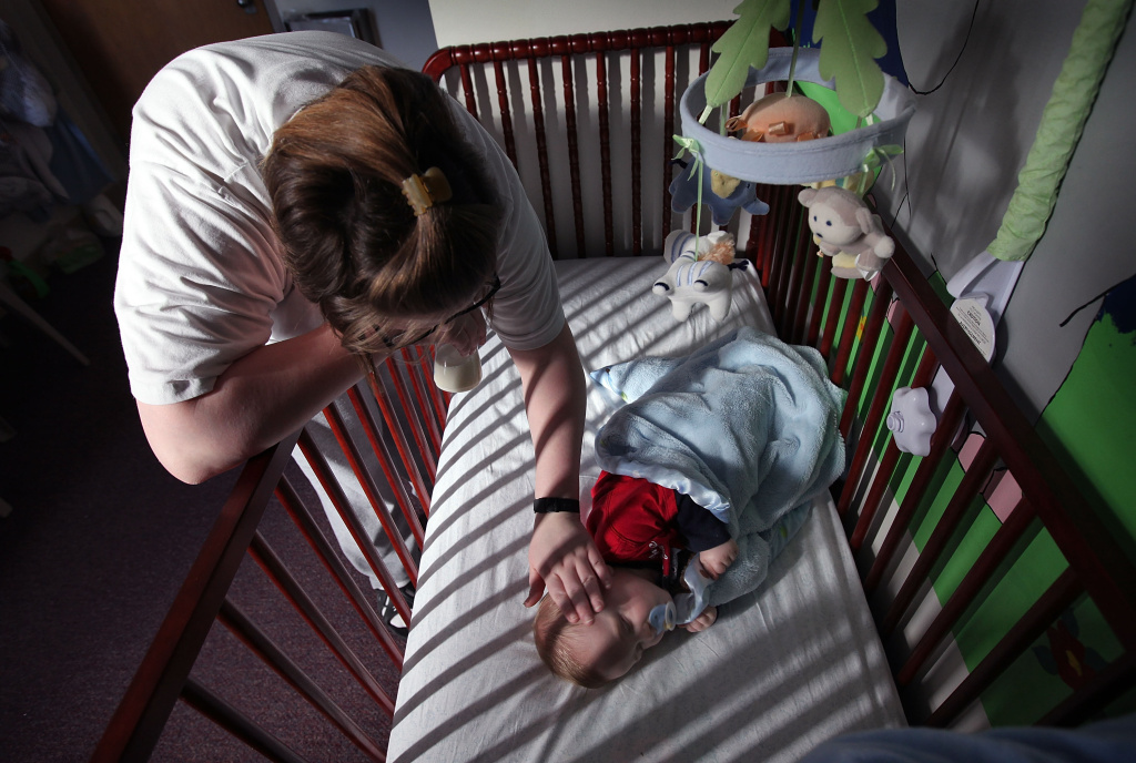 Katrisa Parks puts her eight-month-old son Skyler down for a nap in the room they share.