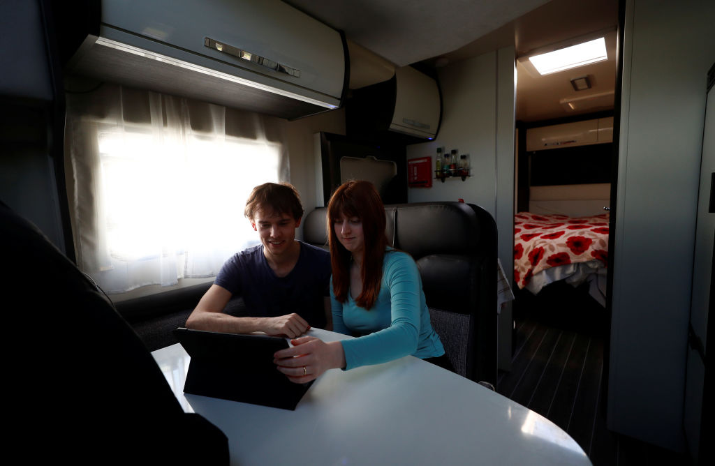 Junior Doctors Jared Leggett and Amy Kitchen watch a film on an iPad, whilst living in a temporary motorhome in the hospital carpark.