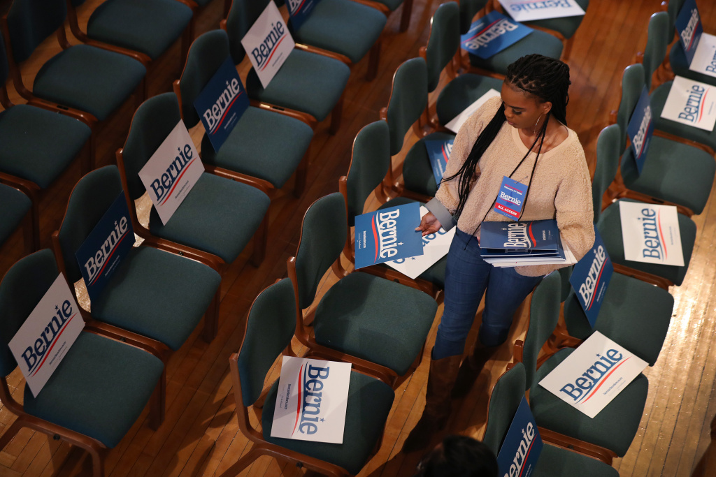 Daja Maxwell places campaign signs on chairs before the arrival of Democratic presidential candidate Sen. Bernie Sanders (I-VT) for a Town Hall campaign event held at the Derry Opera House on February 05, 2020 in Derry, New Hampshire.