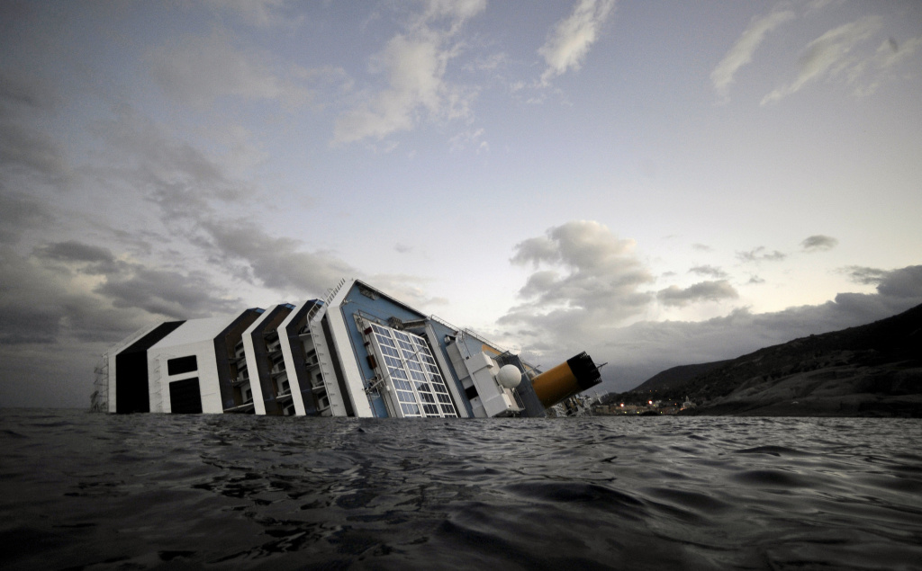 The Costa Concordia cruise ship lies in the harbor of the Tuscan island of Giglio after it ran aground and keeled over off the Isola del Giglio after hitting underwater rocks on January 13.