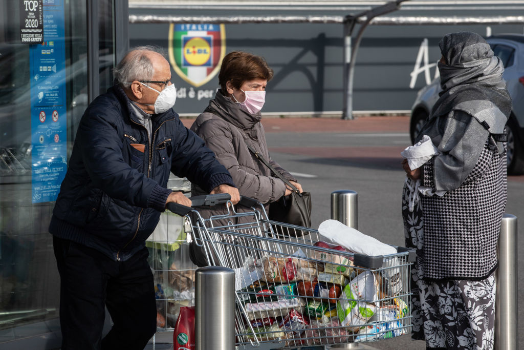 A pair of people wearing respiratory masks push a trolley loaded with foodstuffs after having been given a 10-minutes access to shop in a LIDL supermarket in groups of twenty people on February 23, 2020 in Casalpusterlengo, south-west Milan, Italy.