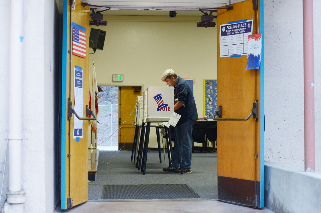 Joe Cigliano stand sin the voting booth as he casts his ballot at Allesandro Elemantary School on March 5, 2013 in Boyle Heights area Los Angeles, California.