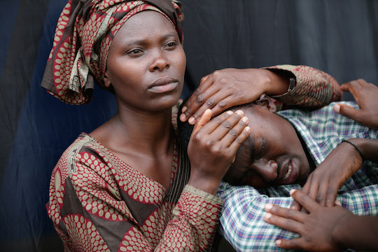 A woman consoles Bizimana Emmanuel, 22, during the 20th anniversary commemoration of the 1994 genocide at Amahoro Stadium April 7, 2014 in Kigali, Rwanda.
