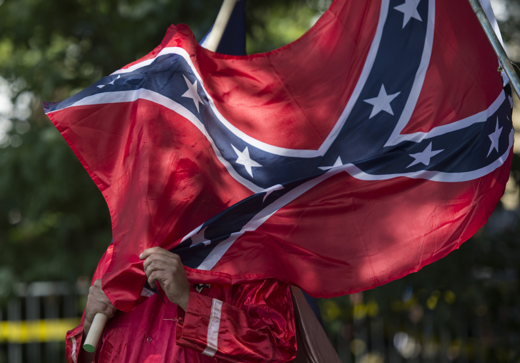 A member of the Ku Klux Klan holds a Confederate flag over his face during a rally, calling for the protection of Southern Confederate monument.