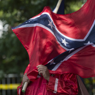 A member of the Ku Klux Klan holds a Confederate flag over his face during a rally, calling for the protection of Southern Confederate monuments, in Charlottesville, Virginia on July 8, 2017. (ANDREW CABALLERO-REYNOLDS/AFP/Getty Images.)