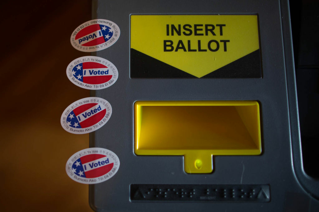 A vote-counting machine and voting stickers.