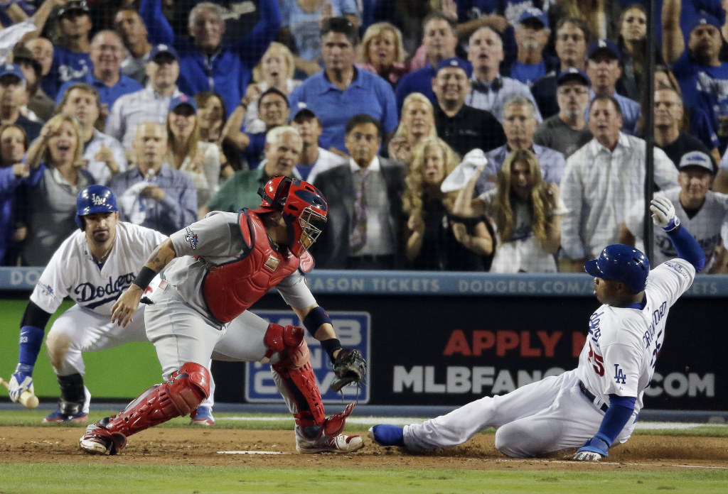 Los Angeles Dodgers' Carl Crawford slides safely past St. Louis Cardinals catcher Yadier Molina during the eighth inning of Game 3 of the National League baseball championship series Monday, Oct. 14, 2013, in Los Angeles.