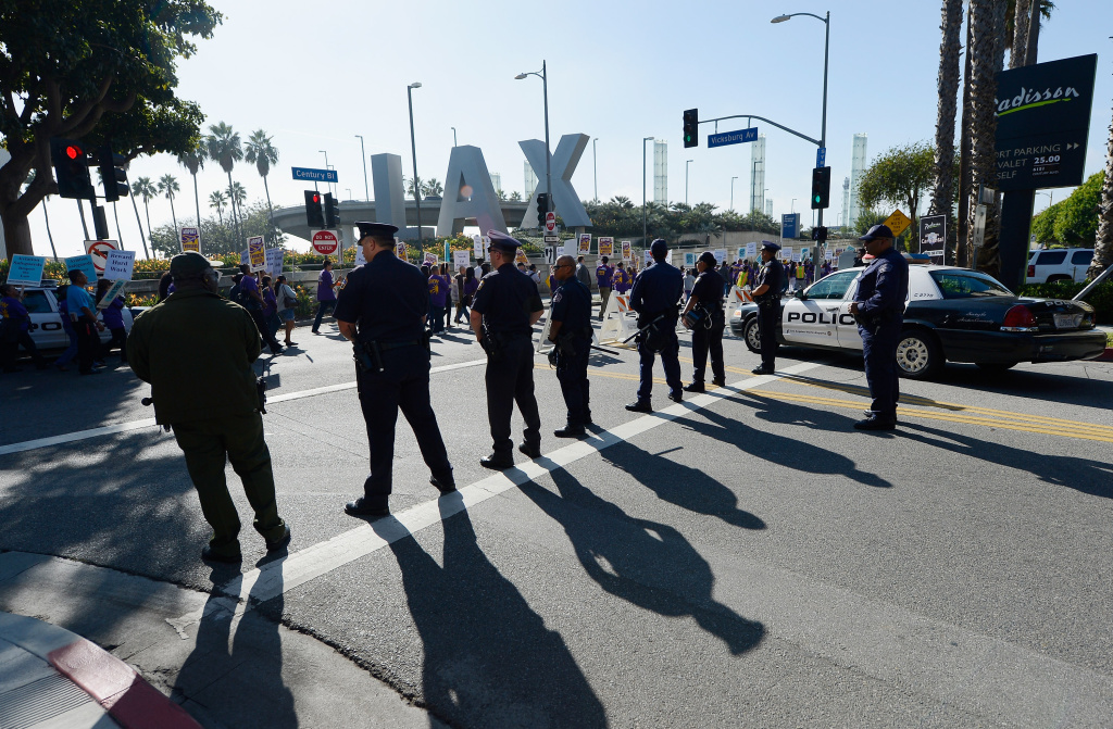 Los Angeles Police department officers look on as a large march by service employees and members from several other unions on the main thoroughfare to the entrance of Los Angeles International Airport during a large protest a day before Thanksgiving, November 21, 2012.