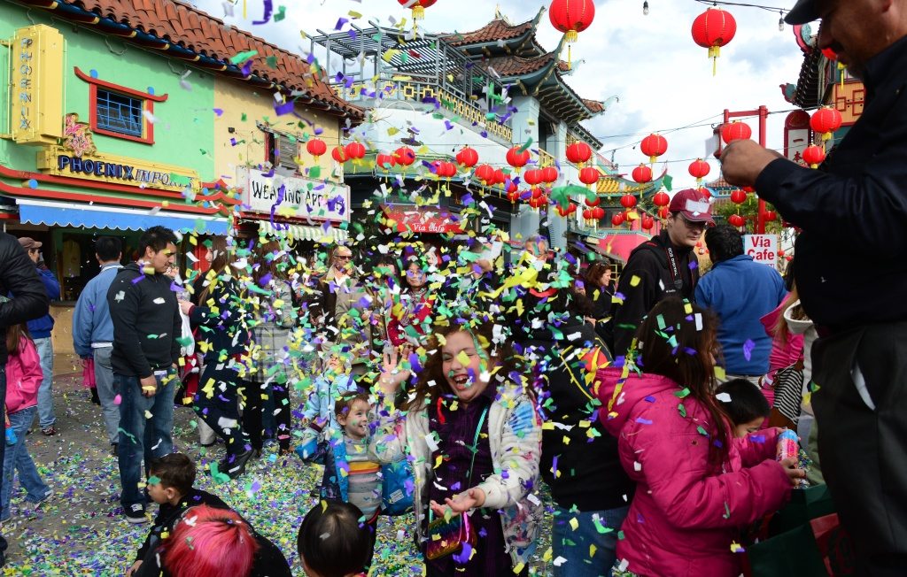 File: Children and adults play amid streamers popping out of firing devices in Chinatown,Los Angeles, California on the third day of Lunar New Year celebrations on February 2, 2014 in the Year of the Horse.