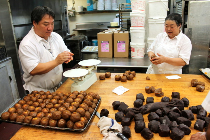 A baker walks past a tray of prepared Mooncakes at Olympic Bakery in Temple City, Calif., Monday September 24, 2012. The small pastries are made for the Chinese Moon Festival which takes place during the eight lunar month each year.