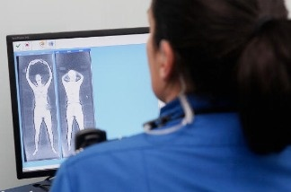 A Transportation Security Administration (TSA) worker demonstrates the monitoring station which will be used with full-body scanners.
