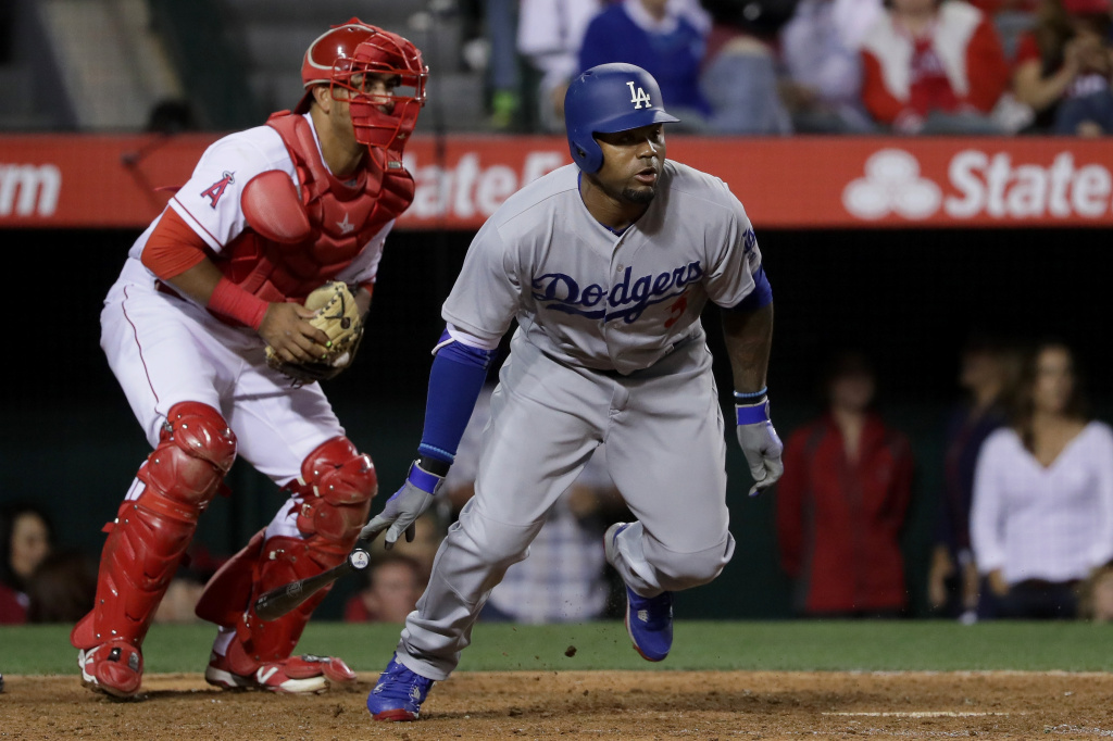 Carl Crawford #3 of the Los Angeles Dodgers runs to first base as Carlos Perez #58 of the Los Angeles Angels of Anaheim stands.
