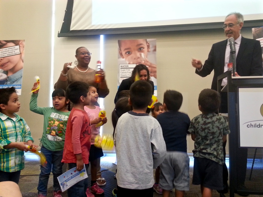Pre-kindergartners at the Los Angeles Children's Bureau near downtown join Dr. Paul Simon, of the department of public health, in a cheer for water at the launch of a health water campaign.