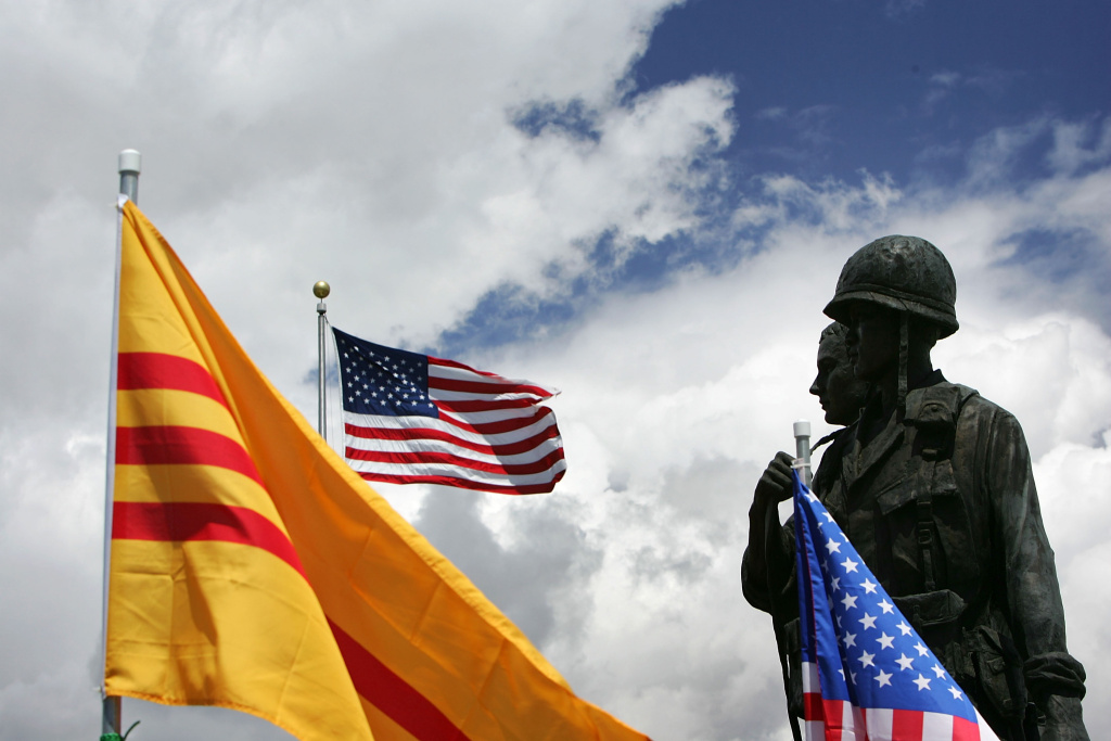 A statue depicting an American and South Vietnamese soldier is surrounded by American and old-style Vietnamese flags at the Vietnam War Memorial on April 28, 2005 near the Little Saigon section in Westminster, California.