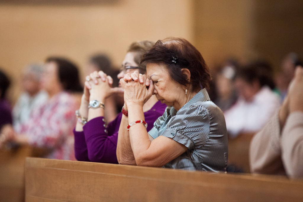 File photo of a woman praying at the Cathedral of Our Lady of the Angels in Los Angeles on March 13, 2013 after the new Pope Francis was announced. A mass on Sunday aims to recognize immigrants.