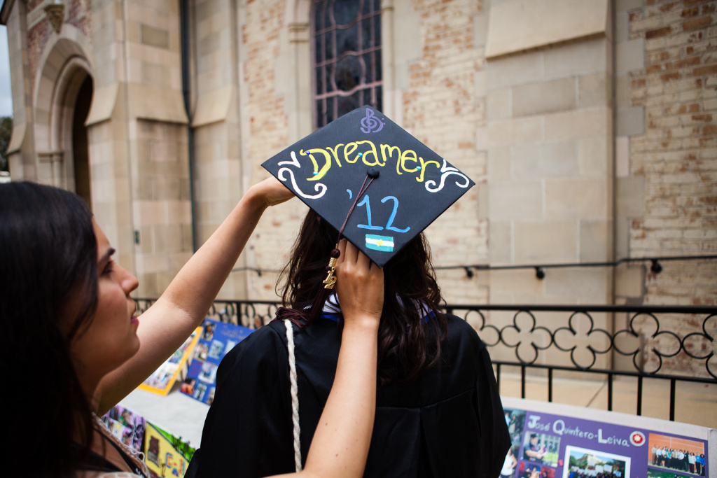 Erica Rey, originally of Argentina, has her cap adjusted by a friend. When she started at UCLA, she was undocumented, but has since become a citizen of the U.S.