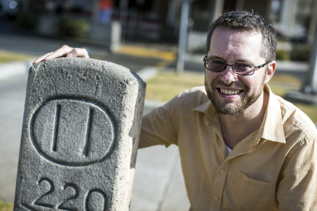 Hidden History's Robert Petersen stands next to a 111-year-old concrete marker on Colorado Boulevard at Holliston Street in Pasadena on Wenesday, June 7, 2017.