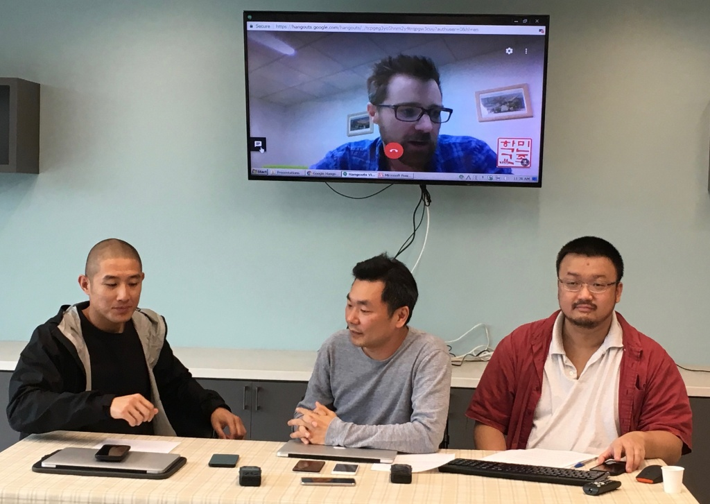 Jungwoo Kim, left, of the Korean Resource Center; Zu Kim, middle, an app developer, and Yongho Kim, right, of the KRC, discuss the new app at a press conference at the center, along with fellow developer Evan Friis, pictured on the screen.