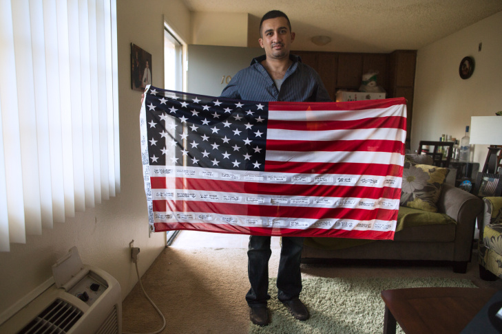 Tariq Abu Khumra, a former translator for U.S. forces in Iraq,  holds an American flag, which was given to him by American troops, in his Glendale apartment.