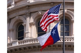 The American and Texas state flags fly outside of the Capitol in Austin, Texas.