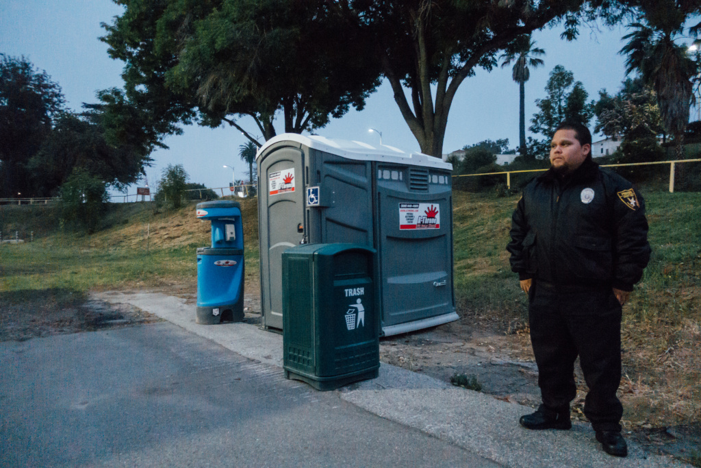 Bill Garcia with Premiere Security Group stands watch at the lot designated for safe parking at the West L.A. VA campus.
