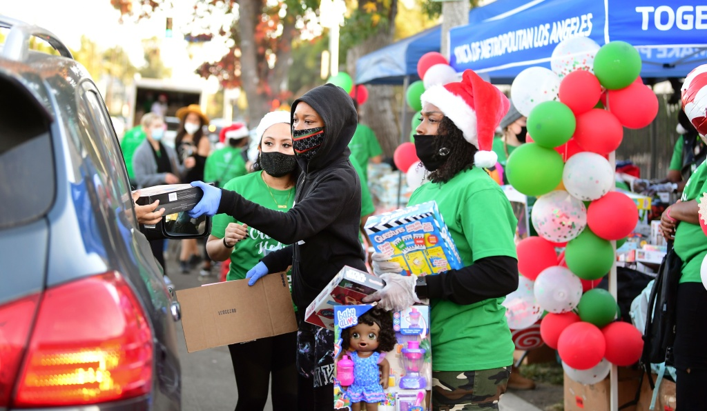 Volunteers wear face masks and Santa hats while delivering gifts to people in passing vehicles at Crenshaw Holiday Spectacular toy and food giveaway and te chance to see Santa Claus in Los Angeles, California on December 13, 2020.