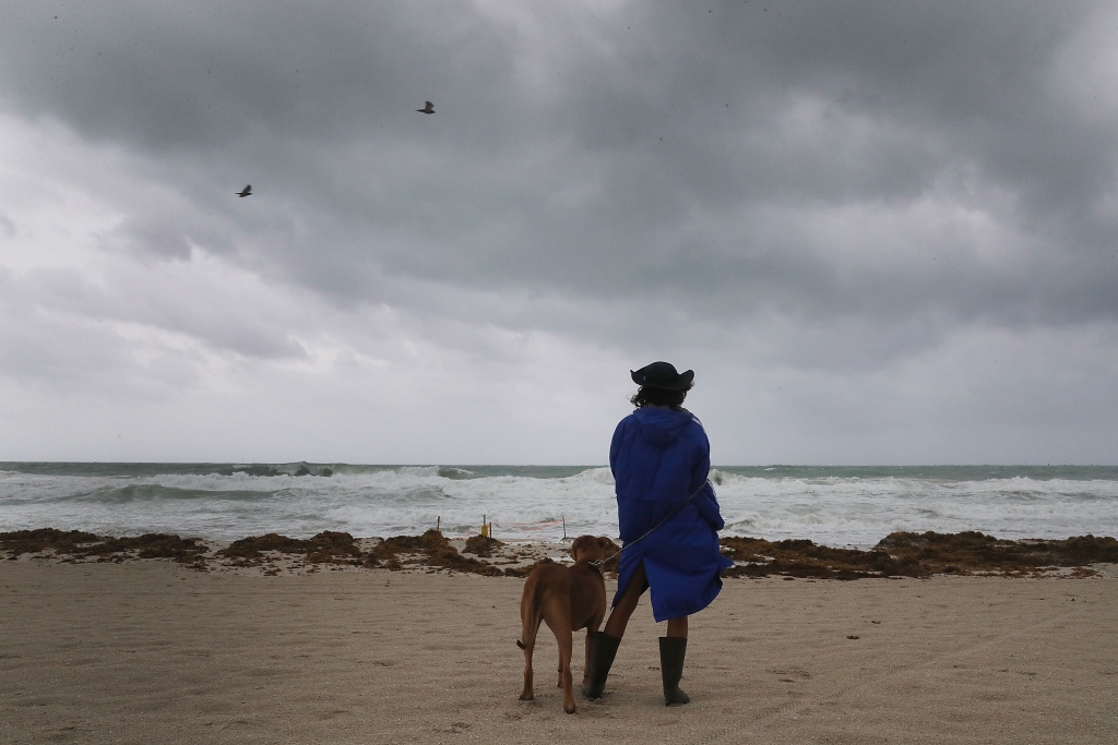 Monica Gutierrez and Tyson look out at the storm clouds and churning ocean as Hurricane Irma approaches on September 9, 2017 in Miami Beach, Florida.