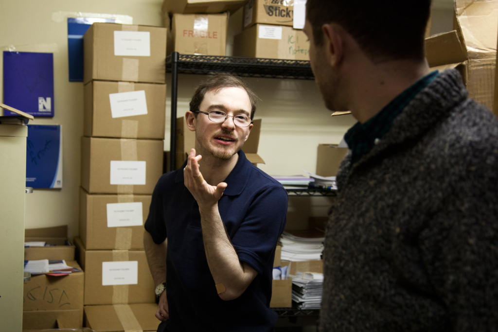 Jonathan Keleher talks with a colleague, Rafael Wainhaus, at work. Keleher was born without a cerebellum, but his brain has developed work-arounds for solving problems of balance and abstract thought.