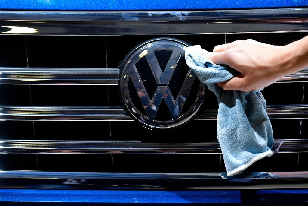A staff member cleans the logo of a VW car on display ahead of the annual general meeting of German carmaker Volkswagen, in Berlin on May 3, 2018.