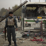 An Afghan police officer stands near some of the wreckage after Saturday's suicide bombing in Kabul.