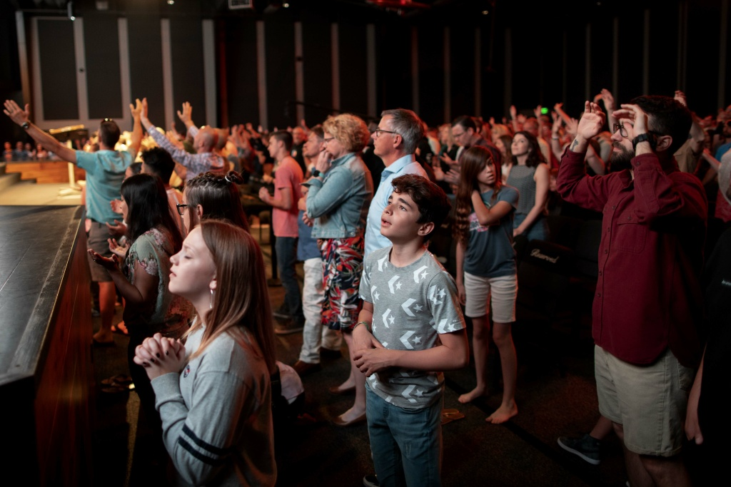Parishioners pray and sing along during Sunday service at Bethel Church in Redding, CA on April 28, 2019.